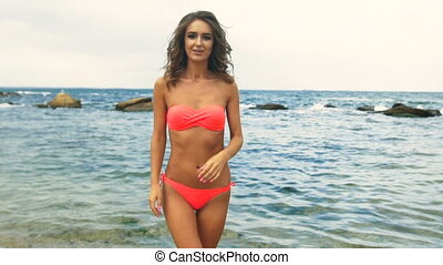 Young slim tanned woman , posing on camera in a beautiful calm beach.