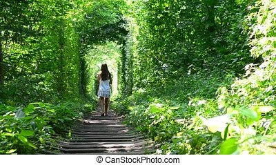 Young slim teenager girl walks away from camera in natural green forest