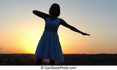 Young Slim Woman Dances Energetically in a Folk Dress at Sunset