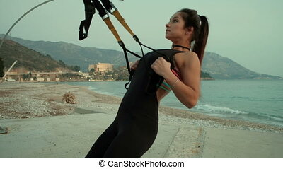 Young slim woman do exercises with strap on beach near ocean.