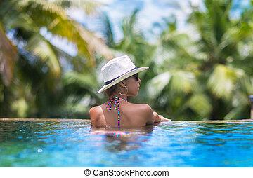 Young slim woman in straw hat getting suntan