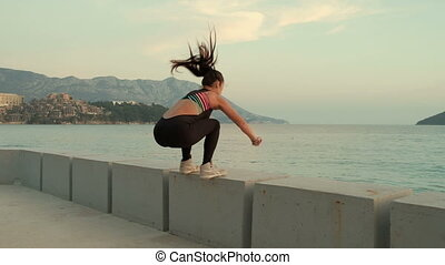 Young slim woman in training suit jump on stone in embankment of sea.