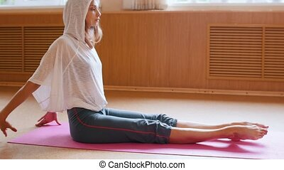 Young slim woman in white hoodie sitting on the yoga mat and...