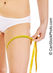 Young slim woman measuring her thigh with a yellow tape
