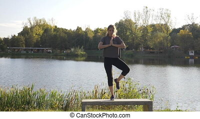 Young slim woman meditating and doing yoga poses standing on one leg in a park to find inner peace in slow motion