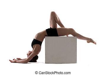 Young slim woman posing on cube in studio