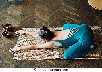 Young slim woman practicing yoga doing child's pose at home