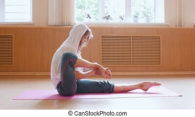 Young slim woman sitting on the yoga mat and puts her legs...