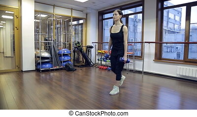 Young slim woman squat with dumbbells as weight in fitness center.