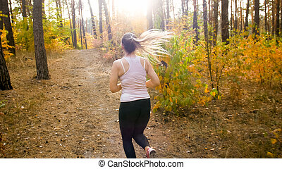 Young slim woman with ponytail jogging in forest at bright sunny day