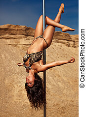 Young slim woman - Young slim pole dance woman on sand...
