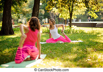 Young slim women doing yoga exercises on the grass in a green park
