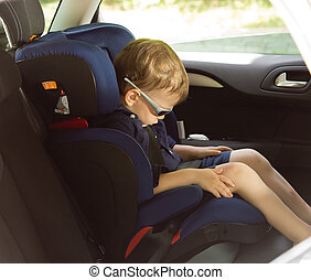 Young small boy sleeping in a child car-seat