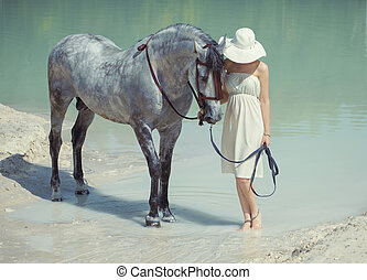 Young smart lady walking with the horse