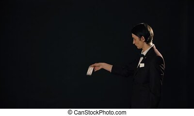 Young smart man showing tricks in the dark - Male...