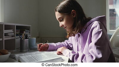Side view focused young smart teen girl reading paper textbook, doing homework alone. School aged pupil sitting at desk, preparing for exam, writing essay or making notes, homeschooling concept.