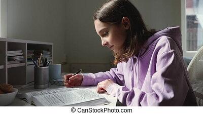 Young smart teen girl reading paper textbook, doing homework...