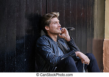 Young smartphone man sitting street