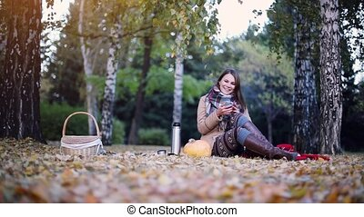 Young smiles woman uses smartphone on a picnic in autumn park sitting the fallen leaves near the pumpkin at Halloween time.