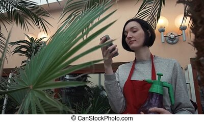 Young smiley girl in red apron taking selfie using smartphone in orangery