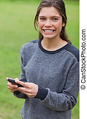 Young smiling adult looking straight at the camera while using her mobile phone