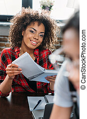 young smiling african american woman holding notebook while sitting at table