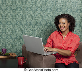 African American woman using a laptop at home