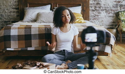 Young smiling african girl recording video blog about...