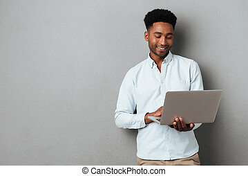 Young smiling african man standing and using laptop