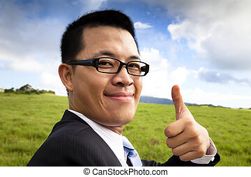 young smiling and confident businessman with thumb up