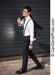 young smiling asian businessman in glasses walking outdoors