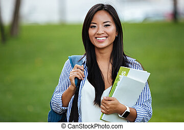 Young smiling asian student woman with backpack, holding notebook, outdoor