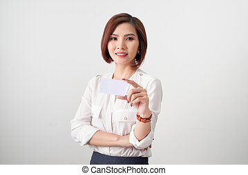 Young smiling asian woman holding a blank card, gesture isolated on white