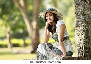 young smiling asian woman sitting outdoor