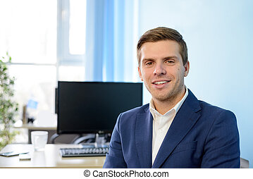 Young Smiling Attractive Businessman in Blue Suit at Modern Office. Business Concept