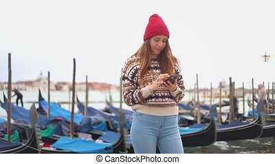 Young smiling attractive woman staying on the waterfront and...