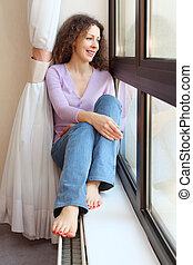 Young smiling barefoot woman sits on windowsill and looks out window