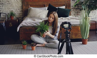 Young smiling blogger in casual clothing is holding flowers,...