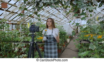 Young smiling blogger woman florist in apron talking and...
