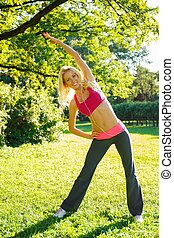 Young smiling blond athletic girl doing exercises on grass in a park and listens to music