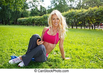 Young smiling blond athletic girl sitting on grass in a park with smartphone and earphones