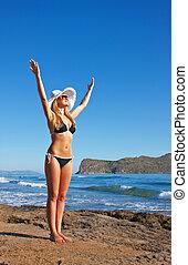 Young smiling blond woman in black bikini