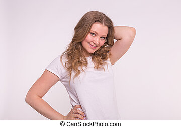 Young smiling blonde woman posing over white background