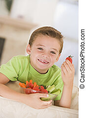 Young smiling boy eating