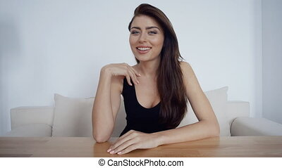 Young smiling brunette businesswoman sitting behind computer, online conference