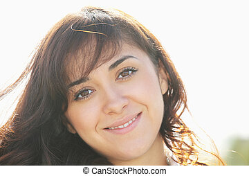 Young smiling brunette in sunlight