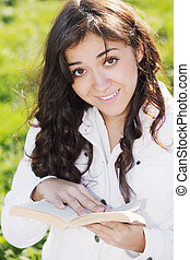 Young smiling brunette in white with book