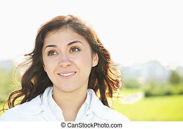 Young smiling brunette looking up