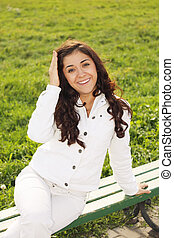 Young smiling brunette sitting on bench