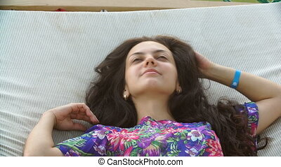 young smiling brunette woman relaxed in hammock on tropical...